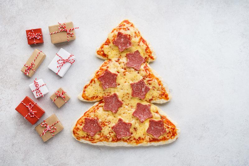 Christmas pepperoni pizza shaped as Xmas tree and gift boxes. On light gray background. Copy space, fir-tree, festive, symbol, restaurant, menu, italian, food stock images