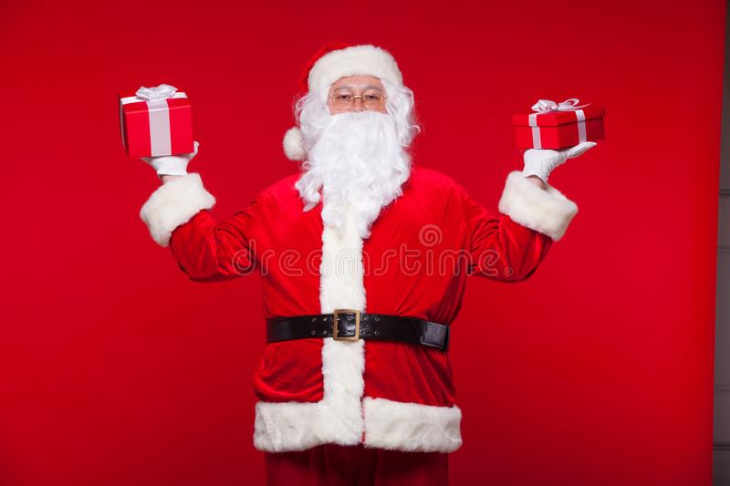 Christmas. Photo Santa Claus giving xmas present and looking at camera, on a red background.  stock photos