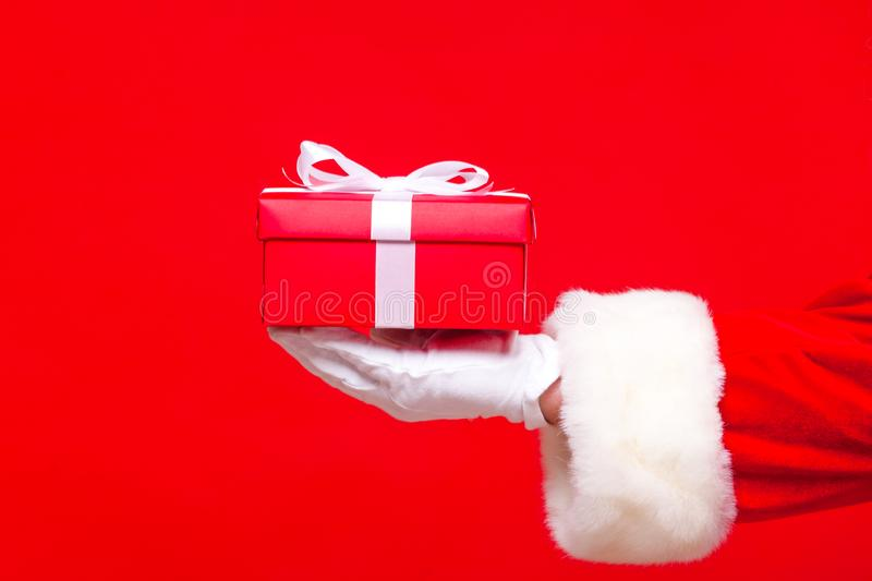 Christmas Photo of Santa Claus gloved hand with red giftbox.  royalty free stock images