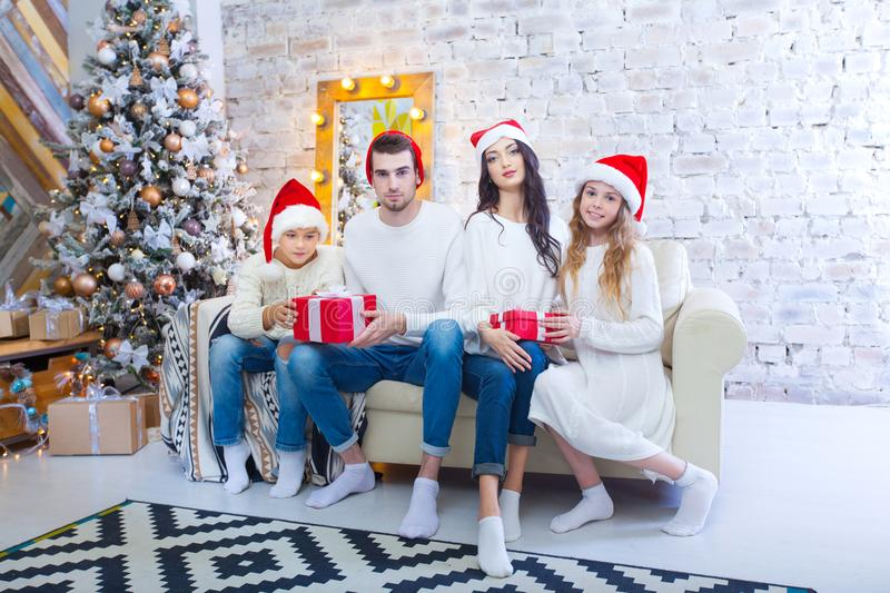 A Christmas photograph of a beautiful family with two children in Santa Claus red caps and red presents. Sit on the. Couch in the Christmas interior stock image