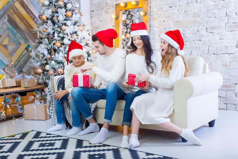 A Christmas photograph of a beautiful family with two children in Santa Claus red caps and red presents. Sit on the. Couch in the Christmas interior royalty free stock photography