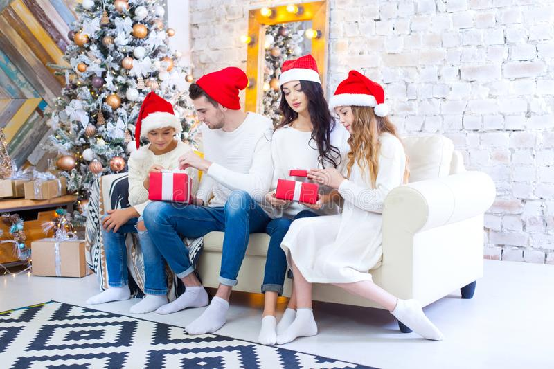 A Christmas photograph of a beautiful family with two children in Santa Claus red caps and red presents. Sit on the. Couch in the Christmas interior royalty free stock image