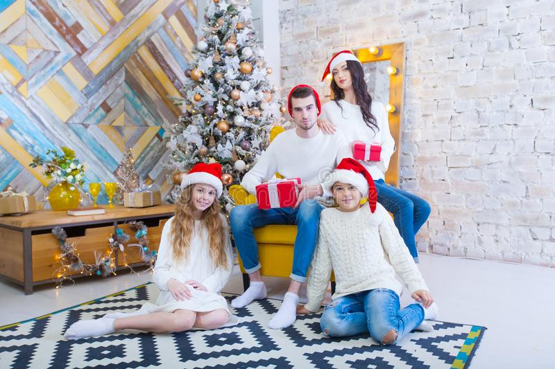 A Christmas photograph of a beautiful family with two children in Santa Claus red caps and red presents. Sit on the. Couch in the Christmas interior stock photo