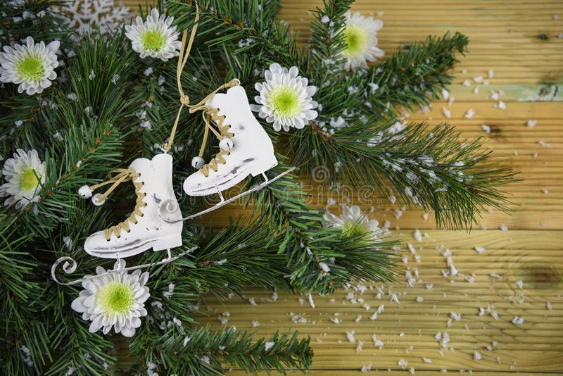 Christmas photography picture with tree branches and ice skating boots decoration and white winter flowers sprinkled with snow stock image