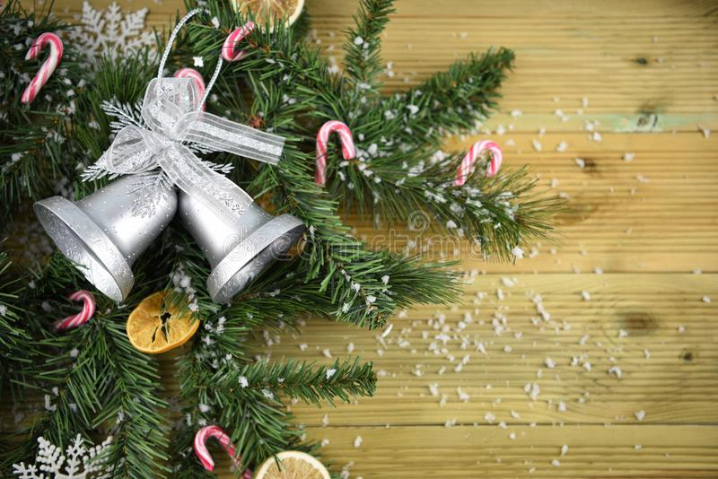 Christmas photography picture with tree branches and silver color bell decoration candy canes and fruit all sprinkled with snow royalty free stock image