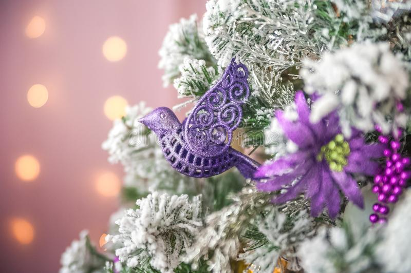 Christmas picture in pink, purple, neon color close up. Scandinavian style of decorating the Christmas tree. Christmas toys such a. S birds, flowers, garlands royalty free stock image