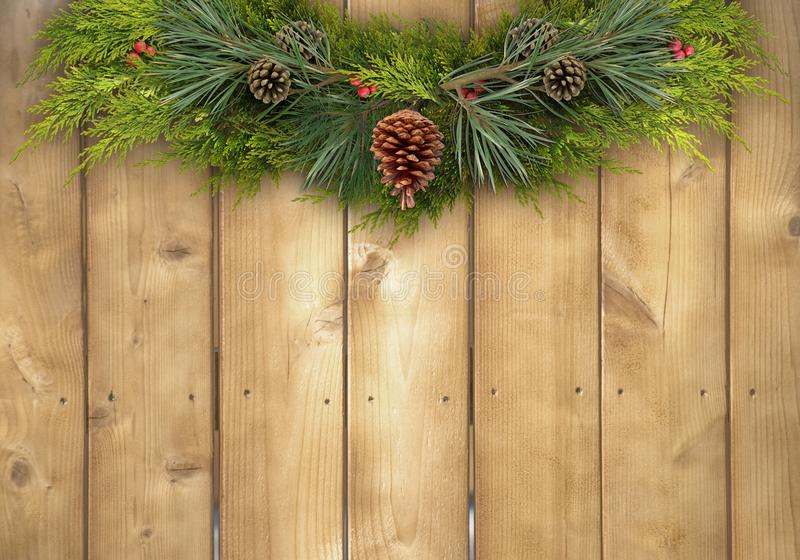 Christmas Pine Garland on a Rustic Wood Fence. Rustic Christmas background of a pine garland with holly berries on a wood fence royalty free stock image