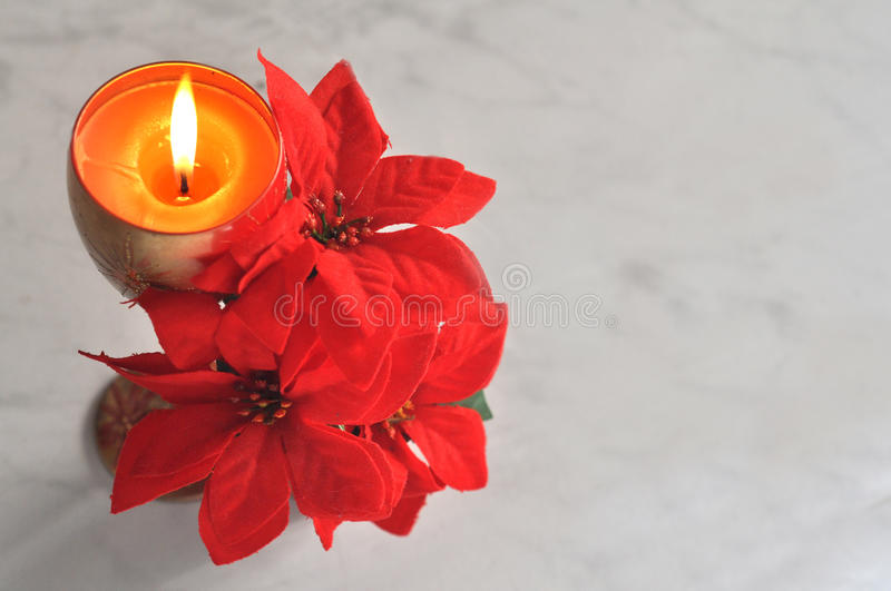 Christmas poinsettia. Lit candle with red poinsettia christmas background royalty free stock images