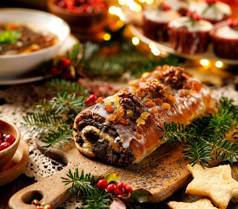 Christmas poppy seed cake,covered with icing and decorated with raisins and walnuts on the holiday table. stock image