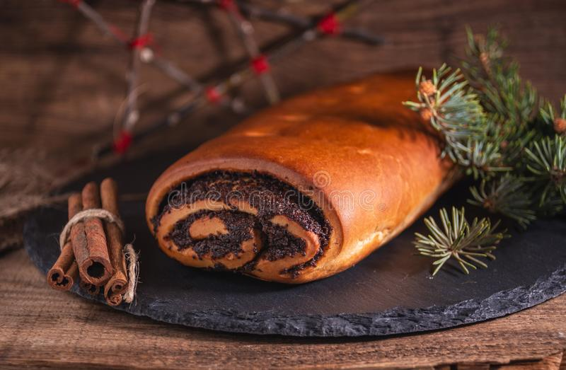 Christmas poppy seeds roll and branch of pine, holiday cake on wooden background stock photography