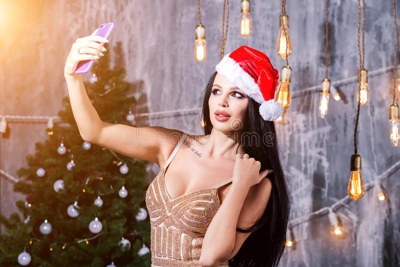Christmas portrait of beautiful girl. woman in evening dress wearing santa claus hat. Girl smiling and making selfie on. Mobile phone. Holidays, New Year stock photos