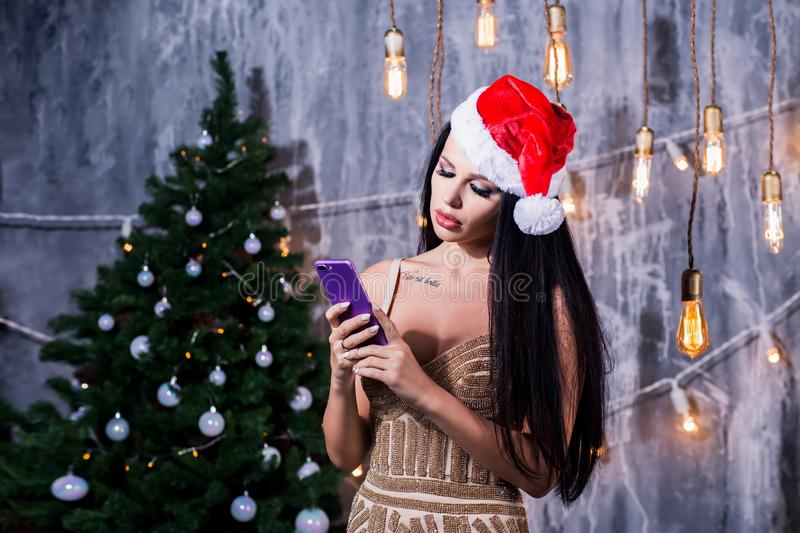 Christmas portrait of beautiful girl. Woman wearing santa claus hat. in the hands holding mobile phone, sad face. Holidays, New Year, celebration and people royalty free stock photo