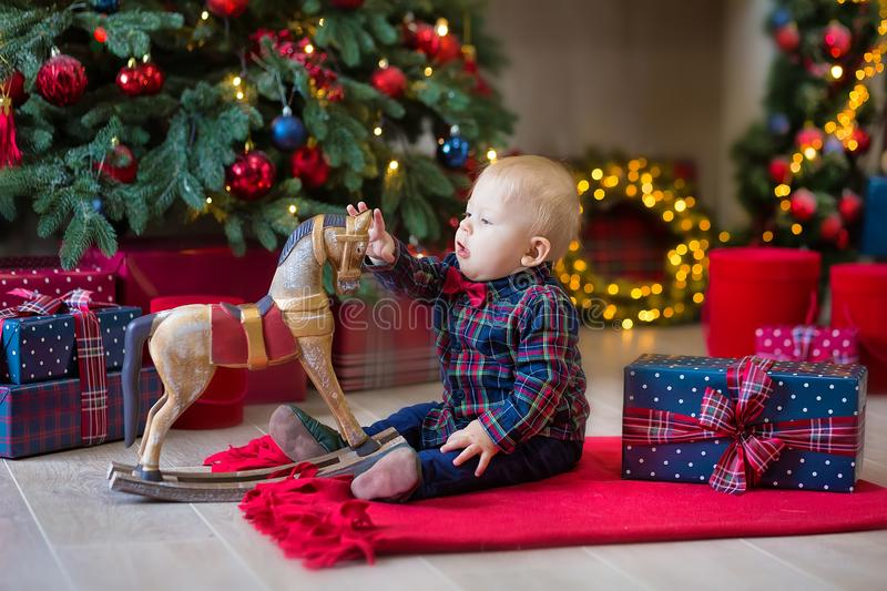 Christmas portrait of cute little newborn baby boy, dressed in christmas clothes and wearing santa hat, studio shot, winter time stock photo