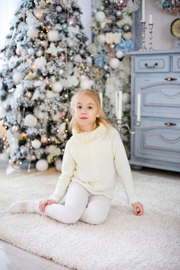 Christmas portrait of happy blonde child girl in white sweater siting on the floor near the Christmas tree. New Year Holidays.  royalty free stock photography