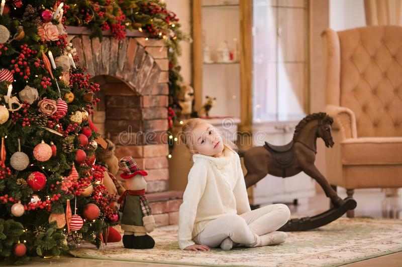 Christmas portrait of happy blonde child girl in white sweater siting on the floor near the Christmas tree and wooden toy horse. N stock photos