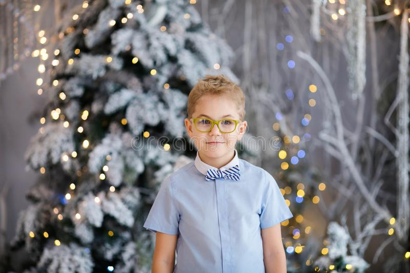 Christmas portrait of happy child boy with big glasses indoor studio, snowy winter decorated tree on background. New Year Holidays. Christmas portrait of happy stock image