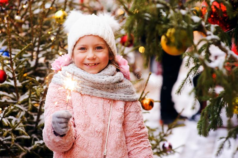 Christmas portrait of happy child girl holding burning sparkler or firework outdoor. Snowy winter decorated tree on background. New Year Holidays in city stock photography