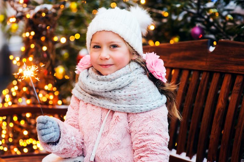 Christmas portrait of happy child girl holding burning sparkler or firework outdoor. Snowy winter decorated tree on background. New Year Holidays in city stock image