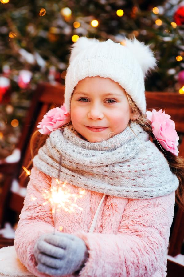 Christmas portrait of happy child girl holding burning sparkler or firework outdoor. Snowy winter decorated tree on background. New Year Holidays in city royalty free stock photos