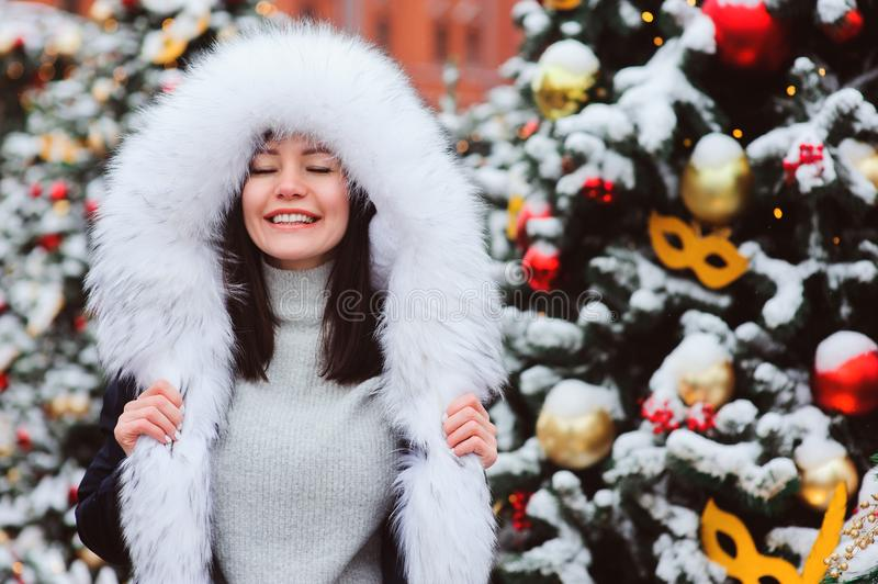 Christmas portrait of happy young woman walking in winter snowy city stock photo
