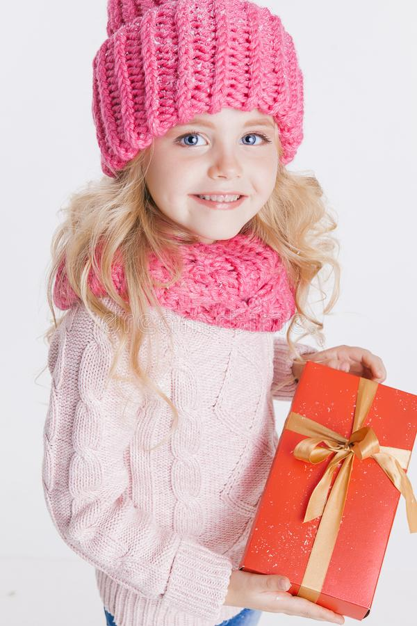 Christmas. Portrait of little curly girl in knitted pink winter hat and scarf on white. Red Present in her royalty free stock photos