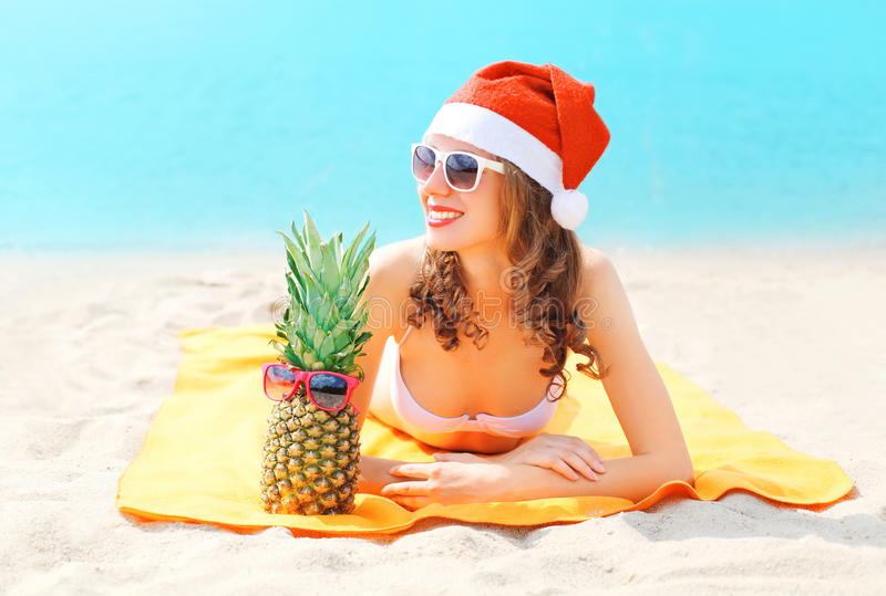 Christmas portrait pretty young woman in red santa hat with pineapple lying on beach sends air kiss over blue sea stock photos