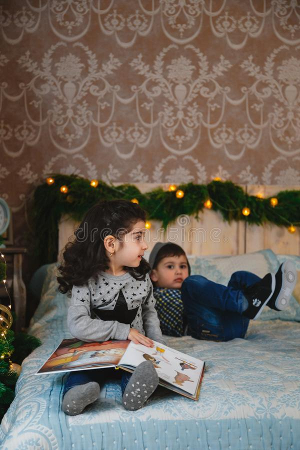 Christmas portrait of small kids sitting on bed with presents under the christmas tree and having fun. Winter holiday Xmas stock photos