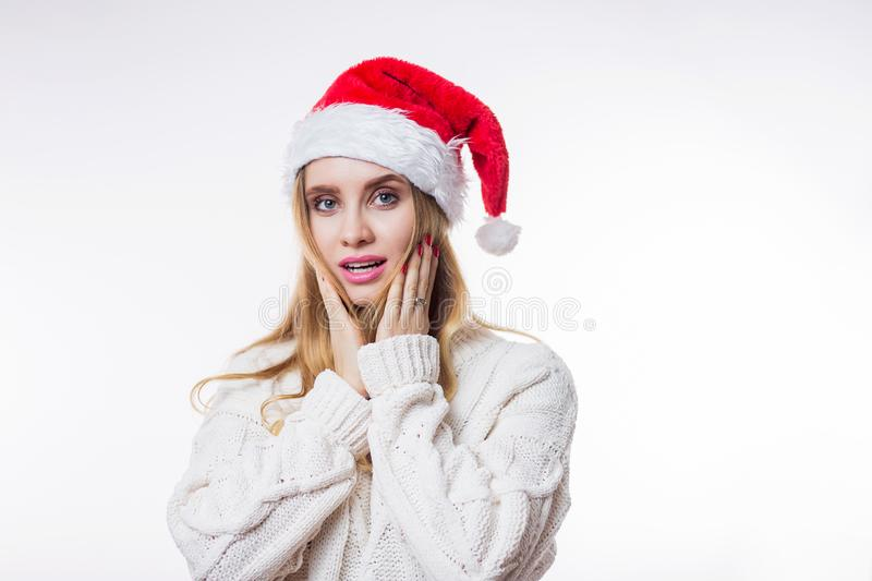 Christmas portrait of surprised and joyful beautiful blonde woman wearing beige knitted sweater, red Santa hat on white background stock photos