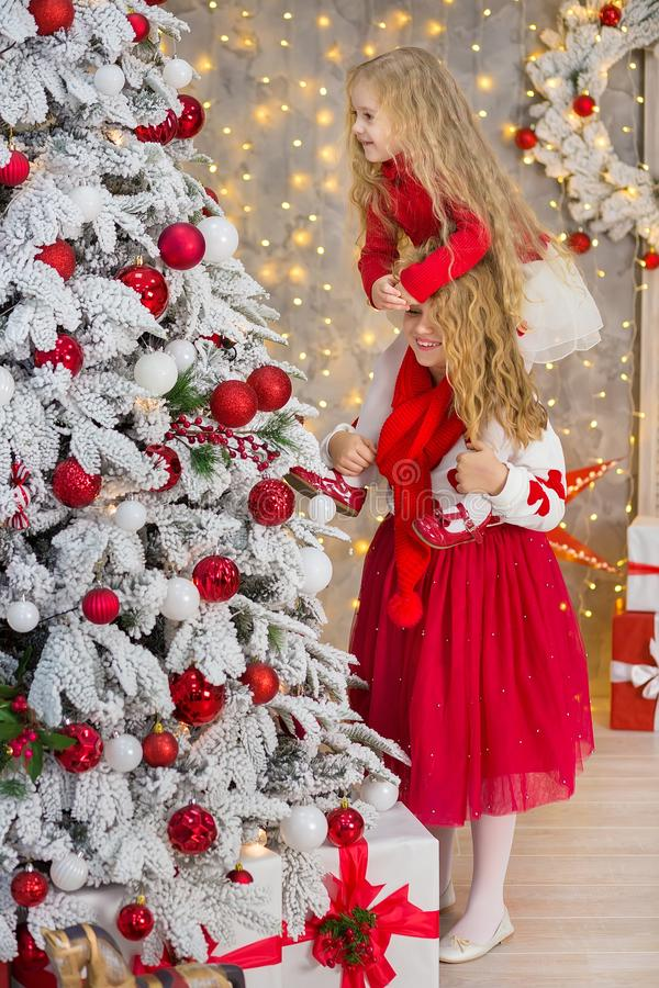 Christmas portrait of two beautyful cute girls Smiling sisters friends and xmas luxury green white tree in unique interior studio stock images