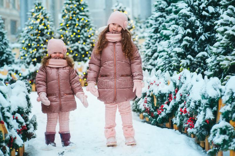 Christmas portrait of two happy sisters playing outdoor in winter snowy city decorated for New Year holidays royalty free stock photo