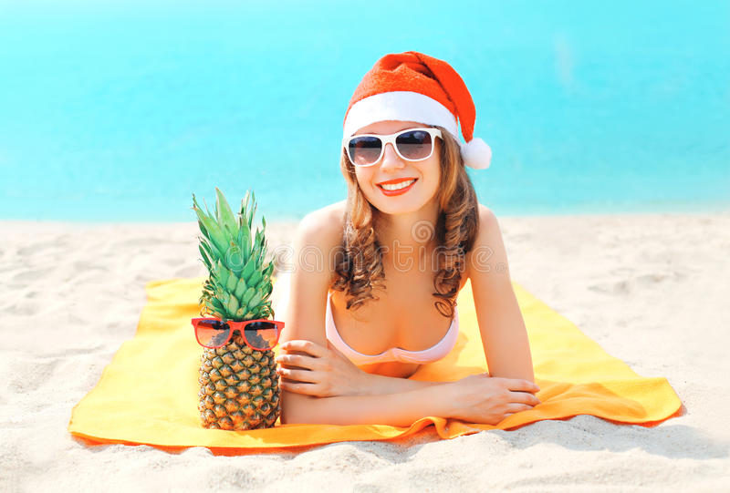 Christmas portrait young smiling woman in red santa hat and pineapple lying on beach over sea stock photo
