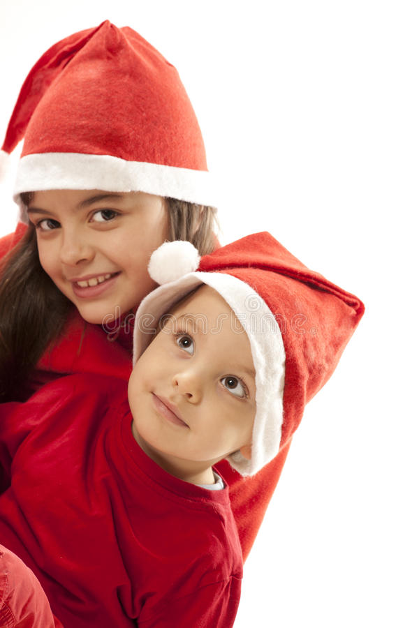 Christmas portrtait. Portrtait of a girl and boy in christmas hats stock photography