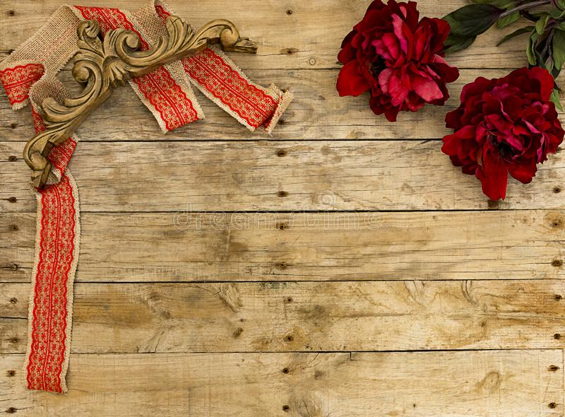 Christmas postcard frame on wooden background for greeting card. Red ribbon with vintage wooden ornament and big flowers. Xmas. stock photography