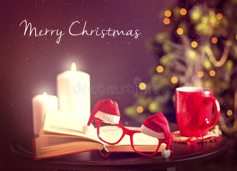 Christmas postcard with Santa glasses. Christmas postcard with funny Santa,s glasses, white candles, and red hot cup with Chriatmas tree on the background stock photography