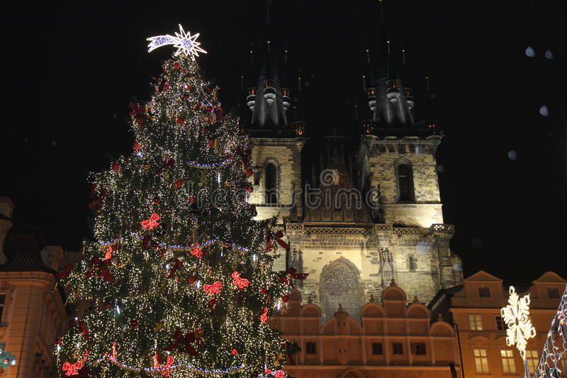 Christmas in Prague. In the Czech Republic with a view of the Church of Our Lady before Tyn, a giant well-lit Christmas tree, star decorations, falling snow royalty free stock photography