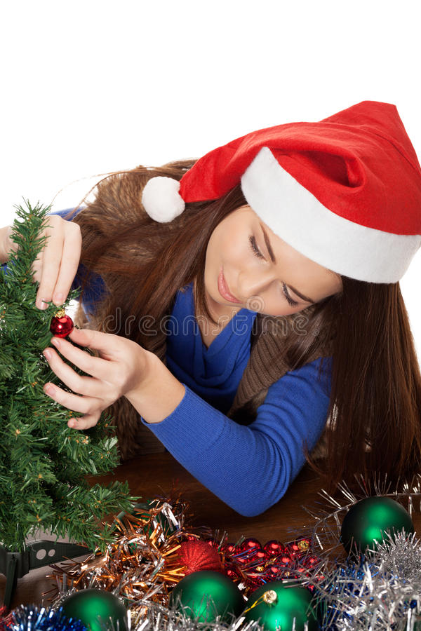 Christmas preparation. Girl in Santa cap preparing for Christmas royalty free stock images