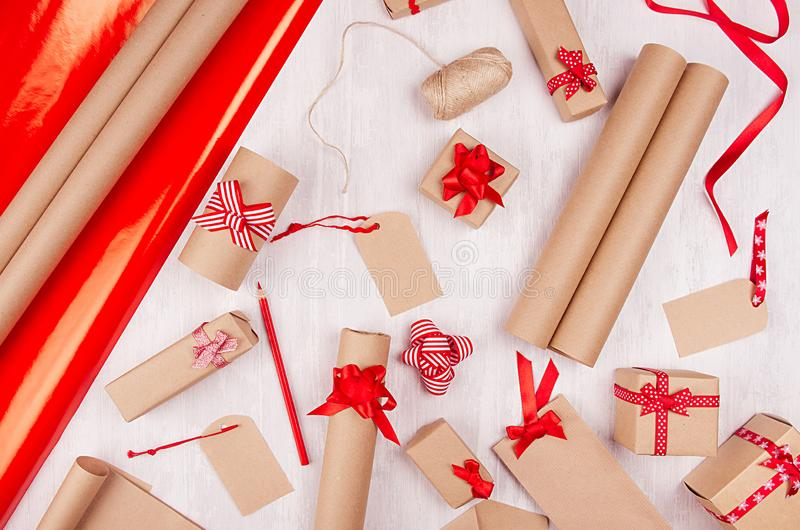 Christmas preparations background - wrapping paper, gift boxes, red ribbon and bows, twine as festive pattern on white wood board. stock photo