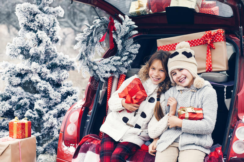 Christmas preparations. Holiday preparations. Pre teen children enjoy many Christmas presents in car trunk. Cold winter, snow weather stock photo