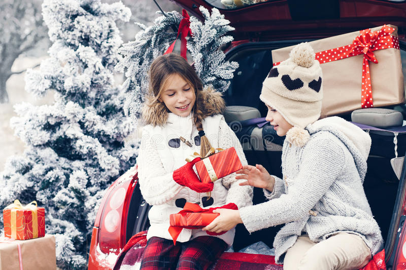 Christmas preparations. Holiday preparations. Pre teen children enjoy many Christmas presents in car trunk. Cold winter, snow weather royalty free stock photos