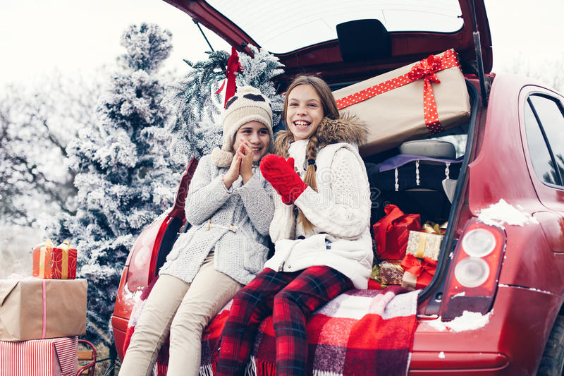 Christmas preparations. Holiday preparations. Pre teen children enjoy many Christmas presents in car trunk. Cold winter, snow weather stock photos