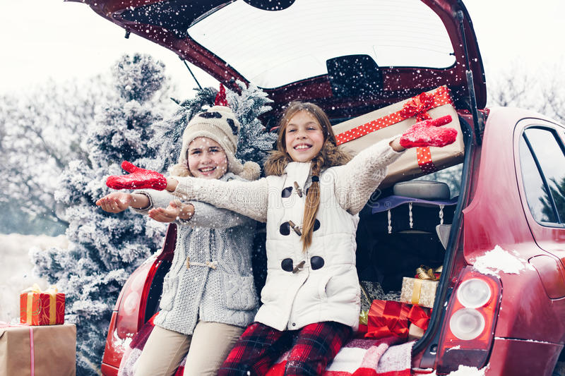 Christmas preparations. Holiday preparations. Pre teen children enjoy many Christmas presents in car trunk. Cold winter, snow weather royalty free stock images