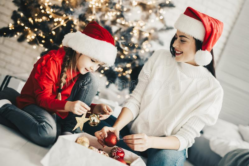 Christmas preparations,Mother decorating home for holidays with. Her daughter royalty free stock photo