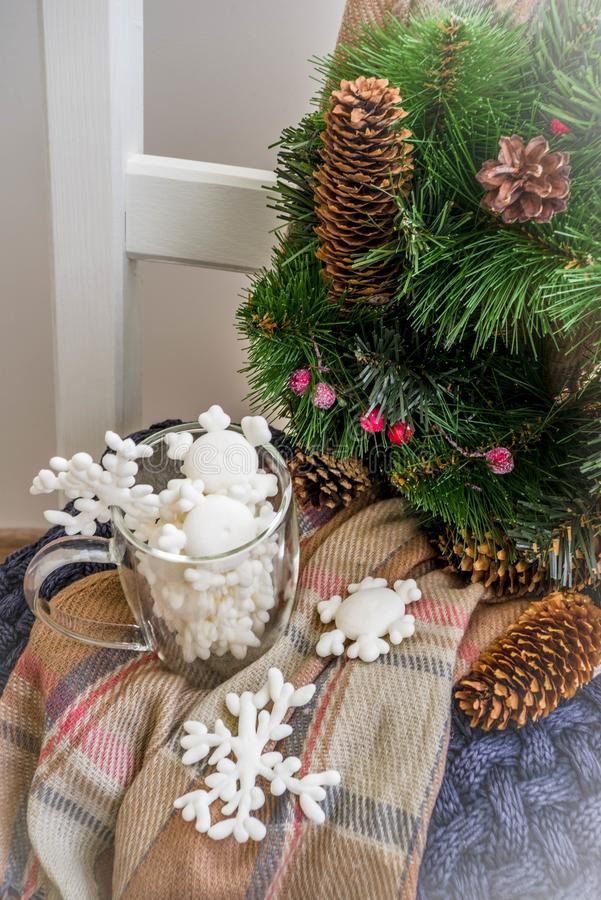 Christmas preparations, new year concept. Home decoration. Domestic interior, warm clothes sweater, plaid, scarf, Christmas tree wreath, with cones, berries royalty free stock photos