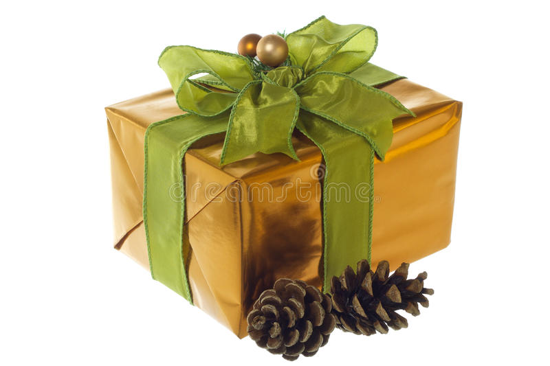 Christmas present. Wrapped in gold paper and tied with a bright green ribbon and a bow royalty free stock photos