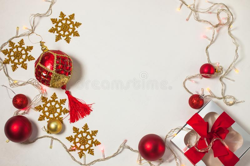 Christmas present box with red ribbon, gold decorations, balls, snowflakes and lights on a white background royalty free stock photography