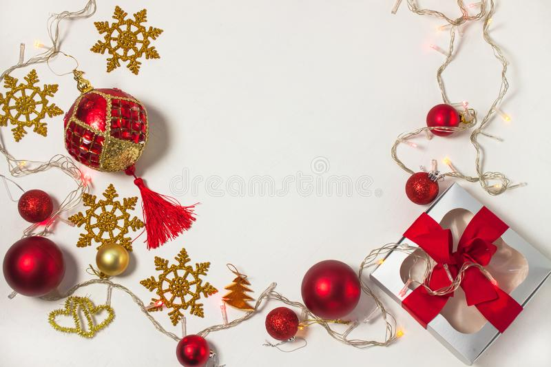 Christmas present box with red ribbon, gold decorations, balls, snowflakes and lights on a white background stock photos