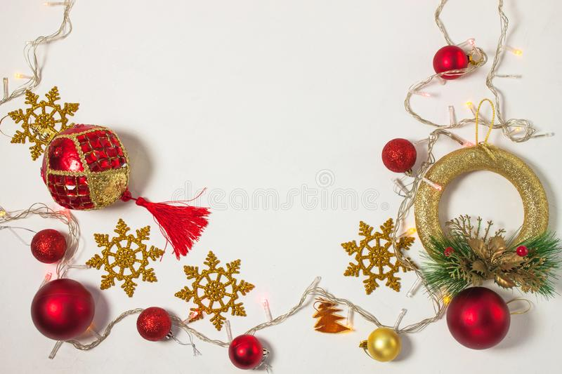 Christmas present box with red ribbon, gold decorations, balls, snowflakes and lights on a white background royalty free stock photo