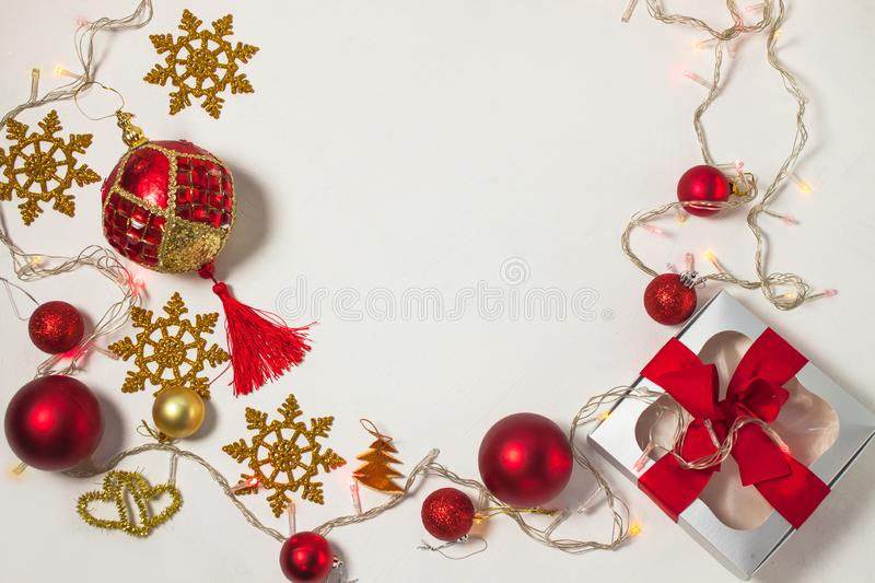 Christmas present box with red ribbon, gold decorations, balls, snowflakes and lights on a white background stock images