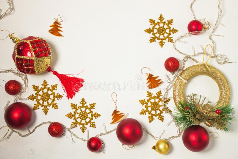 Christmas present box with red ribbon, gold decorations, balls, snowflakes and lights on a white background royalty free stock photos
