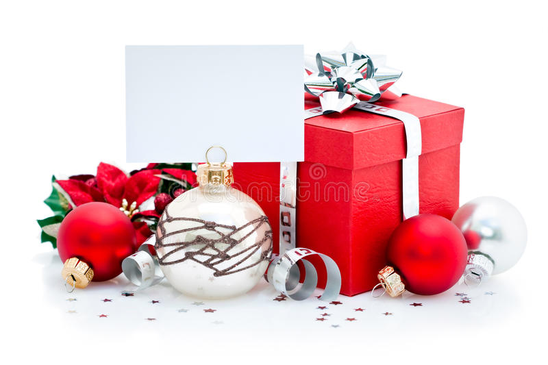 Christmas present and card. Wrapped Christmas present and baubles with blank greetings card or label; isolated on white background royalty free stock images